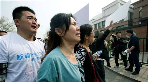 Relatives of Chinese passengers onboard Malaysia Airlines Flight 370 cry as they protest outside the Malaysian Embassy in Beijing, China. (AP)