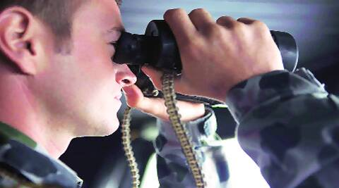 An Australian Navy personnel searches for the missing plane on Sunday. (Reuters)