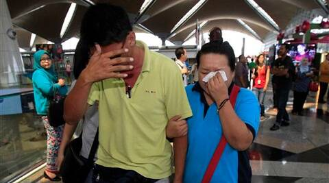 A woman wipes her tears after walking out of the reception center and holding area for family and friend of passengers aboard a missing Malaysia Airlines plane, at Kuala Lumpur International Airport. (AP)