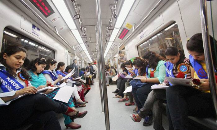 "A group of regular women Metro commuters participate in a fun quiz while enjoying a metro ride on the invitation of DMRC during the launch of its ""Know Your Metro"" campaign for commuters on the occasion International Women's Day in New Delhi on Saturday. (PTI)"
