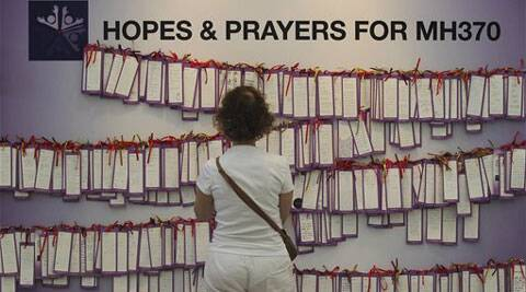 A woman read message cards tied up for passengers aboard a missing Malaysia Airlines plane, at a shopping mall in Kuala Lumpur, Malaysia, Monday, March 24, 2014.