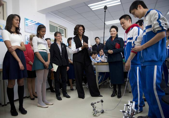 Michelle Obama wore wide-legged black slacks and a loose black vest.<br />Sasha was graceful in a white and navy blue dress which she teamed with knee length socks and shoes. Malia looks chic in green skirt and sweater top.<br />Michelle, Sasha and Malia visited a robotics class. (Reuters)