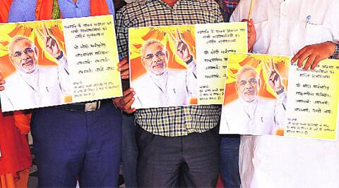 BJP workers hold the poster with 'modified' Durga Saptshati shloka in Varanasi. (IE Photo: Ravi Prakash)