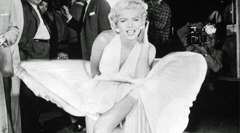 Marilyn Monroe strikes her famous 'upskirt' pose in her white halter dress.