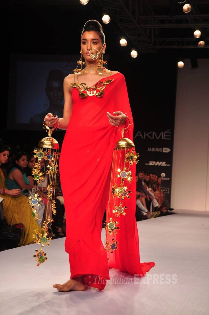 A model walks down the ramp in a bright red sari with oversized dramatic ornaments. (Photo: Varinder Chawla)