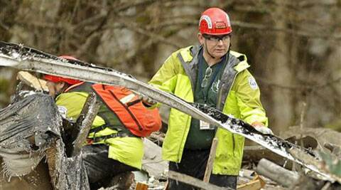 A search and rescue worker clears debris from a house Tuesday, March 25