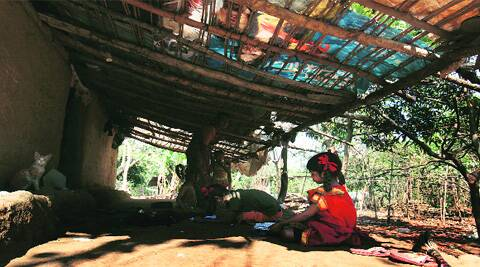 A child studies outside her home in a tribal hamlet at Aarey Colony, which is yet to get electricity. Vasant Prabhu