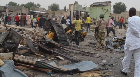 eople gather at the site of a twin car bomb explosion in Maiduguri, Nigeria, Sunday, March 2, 2014.  (AP)