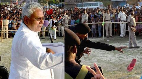 Policemen try to stop a slipper thrown by an unidentified man on Bihar Chief Minister Nitish Kumar during election meeting in Khusrupur on Monday. (PTI)
