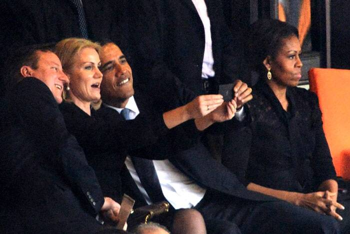 President Barack Obama and British Prime Minister David Cameron leaned to pose for a selfie with Danish Prime Minister Helle Thorning-Schmidt at a vast soccer stadium where Nelson Mandela was honored. Obama's wife, Michelle, sat unsmiling next to her husband, out of the picture, which was captured by a photographer at the event. (AP)