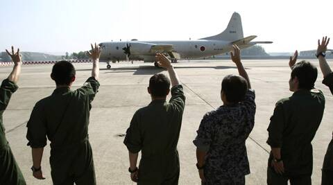 Ground crew members wave to a Japanese Maritime Defense Force P3C patrol plane as it leaves the Royal Malaysian Air Force base heading for Australia to join a search and rescue operation for the missing Malaysia Airlines. (AP)
