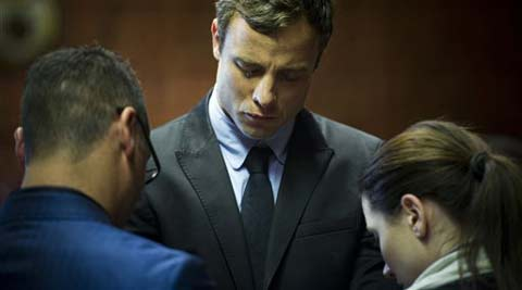 In this Monday, Aug. 19, 2013 file photo, Oscar Pistorius cries as he prays with his sister Aimee, right, and brother Carl in the magistrates court in Pretoria, South Africa. (AP)