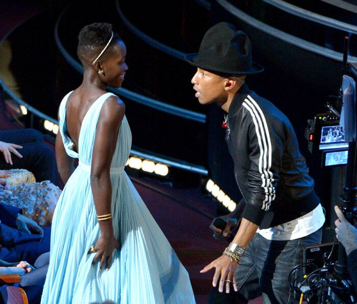 Lupita Nyong'o, left, dances along with Pharrell Williams during his performance of 'Happy' at the Oscars. (AP)