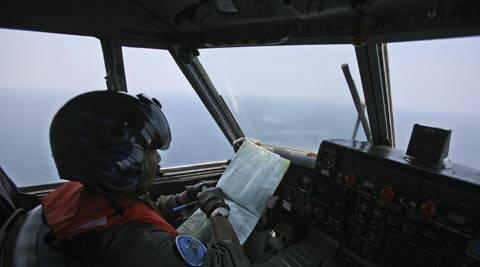 An Indonesian Navy pilot checks his map during a search operation for the missing Malaysian Airlines Boeing 777 over the waters bordering Indonesia, Malaysia and Thailand. (AP)