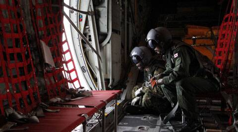 Japanese Air Self-Defense Force's loadmaster Takayuki Ogawa, right, and trained spotter Hiroshi Nakahara scan the ocean aboard a C130 aircraft while it flies over the southern search area in the southeastern Indian Ocean. (AP)