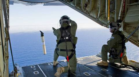 In this photo provided by the Australia Defence Department, Royal Australian Air Force Loadmasters Sgt. Adam Roberts, left, and Flight Sgt. John Mancey, launch a Self Locating Data Marker Buoy from a C-130J Hercules aircraft in the southern Indian Ocean as part of the Australian Defence Force's assistance to the search for Malaysia Airlines flight MH370. (AP)
