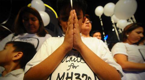 A young Malaysian boy prays, at an event for the missing Malaysia Airline, MH370, at a shopping mall, in Petaling Jaya. (AP)