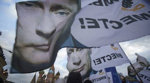 "People rally in support of Crimea joining Russia, with banners and portraits of Russian President Vladimir Putin, reading ""We are together,"" in Red Square in Moscow, Tuesday. (AP)"