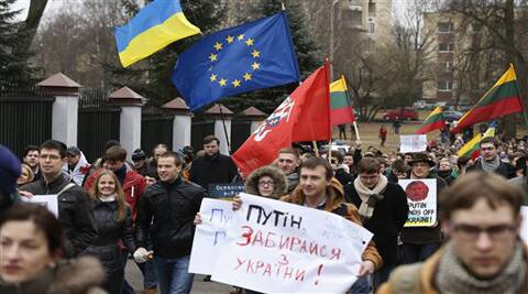 "Demonstrators gather outside the Russian Embassy in Vilnius, Lithuania, to protest against Russian intervention in Ukraine Sunday, March 2, 2014. Poster reads ""Putin out of Ukraine"".  A convoy of Russian troops rolled toward Simferopol, the capital of Ukraine's Crimea region, a day after Russian forces took over the strategic Black Sea peninsula without firing a shot. The parliament in Moscow gave President Vladimir Putin a green light Saturday to use the military to protect Russian interests in Ukraine. (AP)"