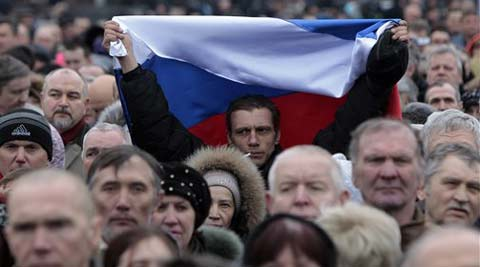 A man holds up a Russian flag during a pro Russian rally at a central square in Donetsk, Ukraine, Sunday, March 9, 2014. (AP Photo)