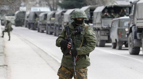 Armed servicemen wait in Russian army vehicles outside a Ukranian border guard post in the Crimean town of Balaclava, March 1. (Reuters)