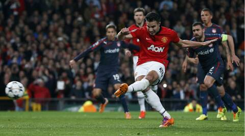 Robin van Persie scores a penalty against Olympiakos during their Champions League clash. (Reuters)