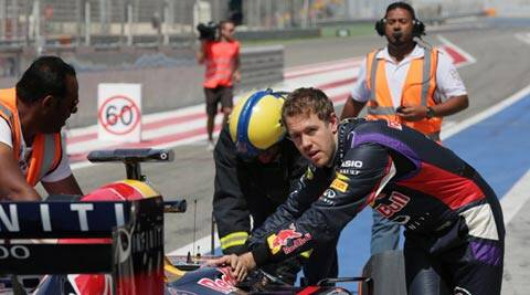 Four-time champion Sebastian Vettel helps push his Red Bull back to the garage after breaking down during pre-season testing in Bahrain, earlier this week. The 2014 season begins in Melbourne a week from now (AP)