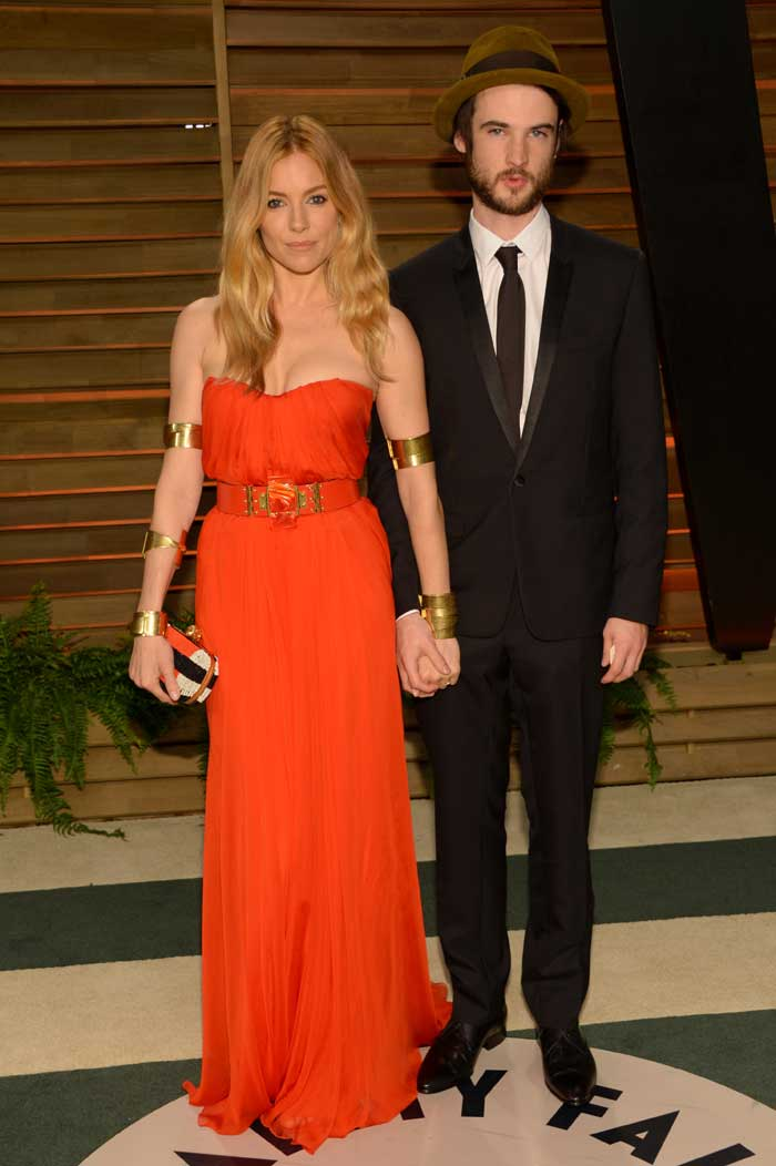 Sienna Miller poses with Tom Sturridge.<br />Sienna Miller who accesorised her look with gold mettalic armlets, bangles and belt.  (AP)