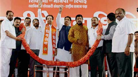 Shiv Sena leader Uddhav Thackeray, BJP leader Gopinath Munde and Republican Party of India president Ramdas Athawale at a meeting in Mumbai on Sunday. (PTI Photo)
