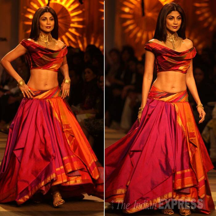 Shilpa Shetty showed off her toned midriff on the ramp in a stunning maroon and orange lehenga choli with rich gold accessories. (IE Photo: Amit Mehra)