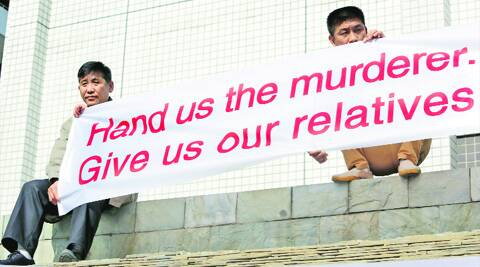 Family members of passengers onboard MH370 hold a banner during a protest outside Lido Hotel in Beijing Saturday. (Reuters)