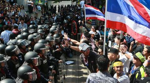 Thailand's riot police standing guard as anti-government protesters stage a rally outside the headquarters of ruling Pheu Thai party in Bangkok. (AP)