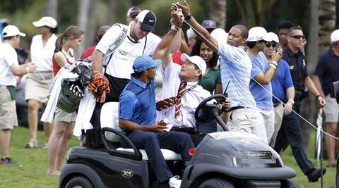 A spectator lifts up a rope for Tiger Woods after play was suspended due to inclement weather (AP)