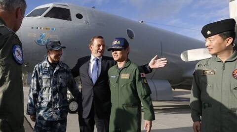Australian Prime Minister Tony Abbott, center, gathers for a picture in front of a Royal Australian Air Force AP-3C Orion aircraft with the leaders of Chinese, Japanese and South Korean military efforts searching for the missing Malaysia Airlines Flight MH370. (AP)