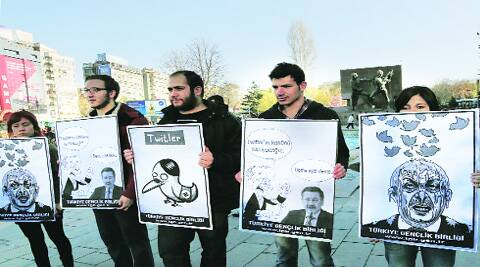 Members of the Turkish Youth Union hold cartoons depicting PM Recep Tayyip Erdogan during a protest against Twitter ban