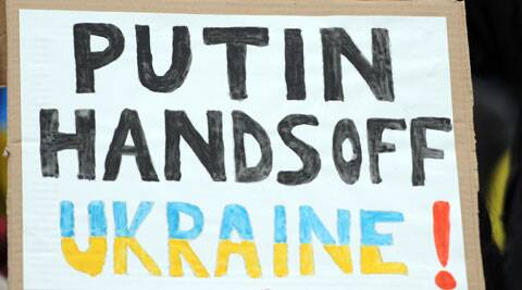 A demonstrator holds a poster reading 'Putin, Hands off Ukraine' during a demonstration in front of the Russian embassy in Berlin, Germany. (AP)