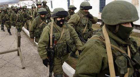 Unidentified armed men patrol around a Ukraine's infantry base in Perevalne, Ukraine, Sunday, March 2, 2014.
