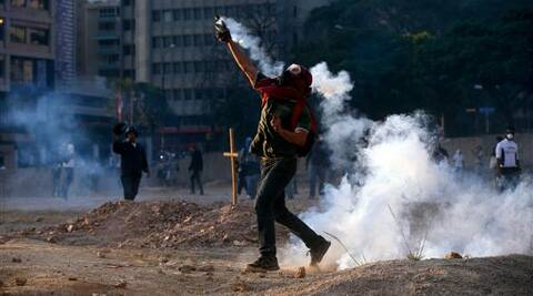A demonstrator returns teargas to Bolivarian National Police during clashes in Caracas. (AP)