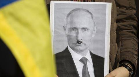 A demonstrator holds a picture of Russian President Vladimir Putin with a beard reading the German word for Crimea during a solidarity demonstration for the Ukraine. (AP)