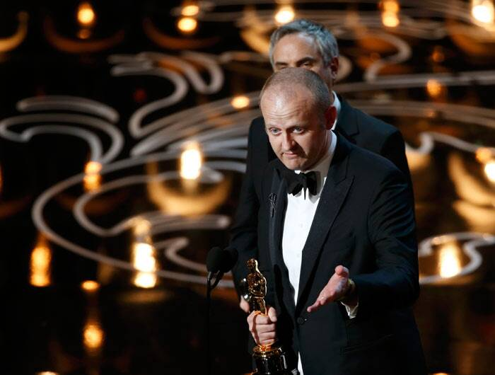"Best Film Editing: Gravity<br /><br />  Alfonso Cuaron (background) and Mark Sanger accept the Oscar for film editing for ""Gravity""  (Reuters)"