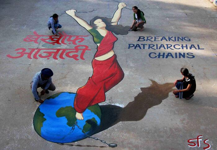 Artists giving the final touches to a painting in Chandigarh on the eve of International Women's Day. (PTI)