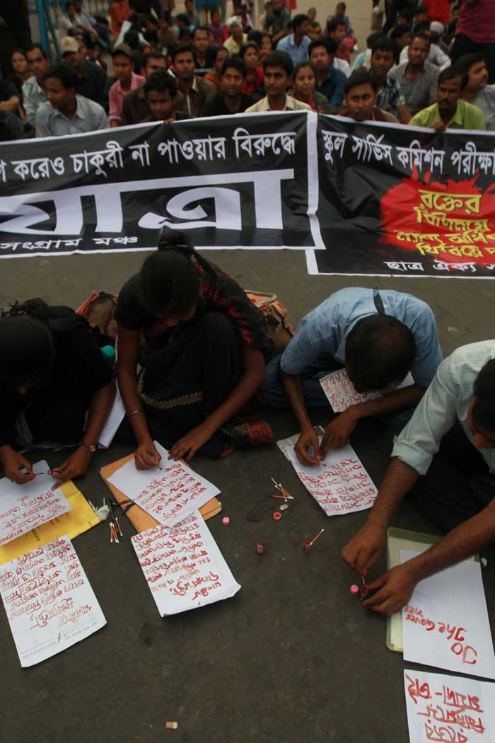 Empanelled candidates of School Service Examination writing letters to Chief minister and other ministers using their blood during a protest rally to demanding service at Esplanade on Friday. (Express photo by Subham Dutta)