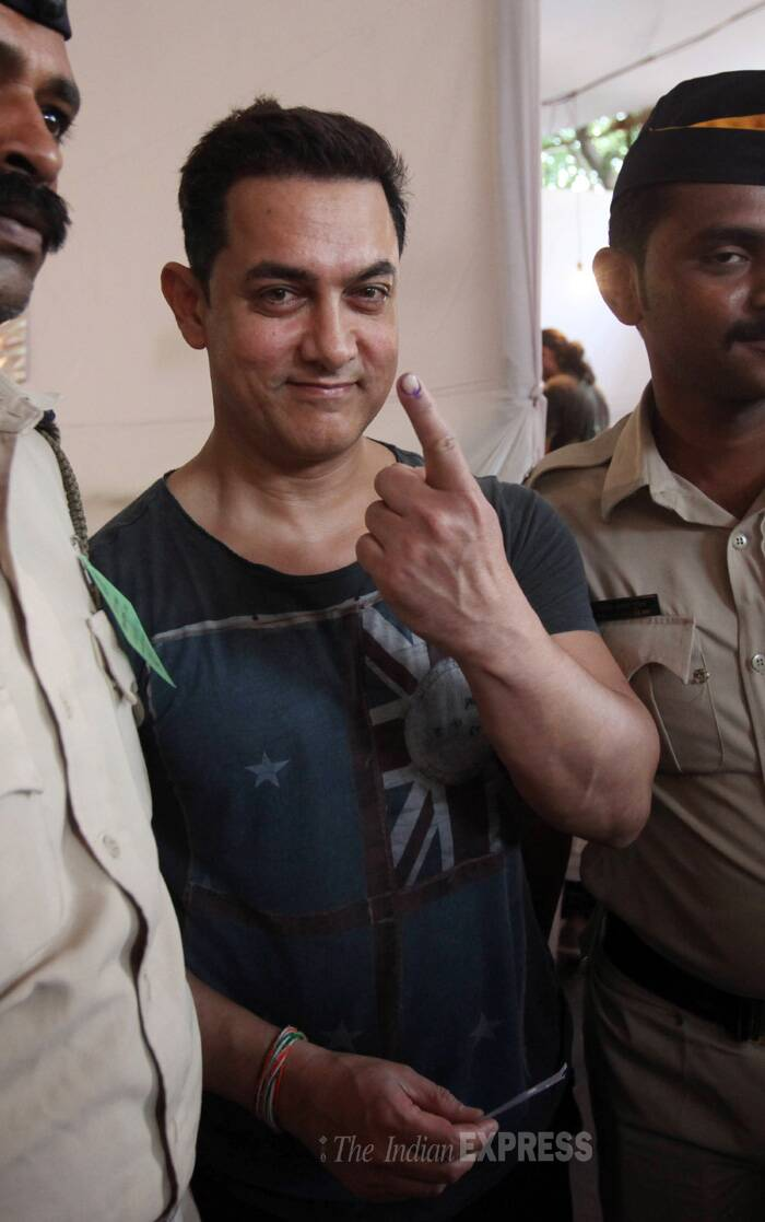 Aamir Khan holds up his ink-stained finger as he leaves after casting his vote at a polling centre.  (IE Photo: Pradip Das)