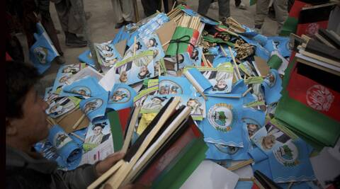 Afghan men collect flags of Afghan presidential candidate Ashraf Ghani Ahmadza outside a stadium where he arrived for an election campaign rally in Kabul, Afghanistan, Tuesday, April 1, 2014. Elections will take place on April 5, 2014. (AP Photo)