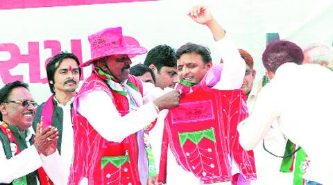 SP leaders help Akhilesh Yadav wear a traditional Gujarati dress in Patan on Monday. Javed Raja