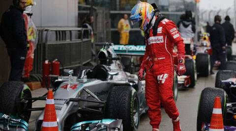 Ferrari F1 driver Fernando Alonso looks at the pole-sitter Lewis Hamilton's Mercedes after the qualifying session in Shangai. (Reuters)