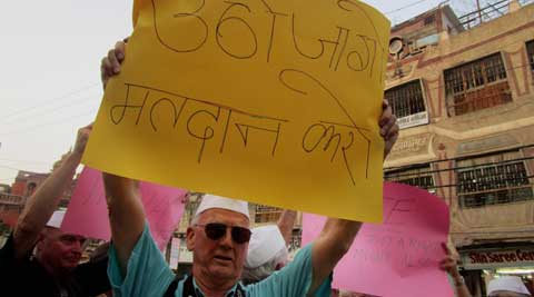 A group of American tourists display placards urging people to vote during the ongoing Lok Sabha elections, as part of an election-themed tour of the holy city of Varanasi. (PTI Photo)