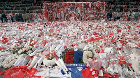 In this file photo dated April 17, 1989, floral tributes are placed by football fans at the 'Kop' end of Anfield Stadium in Liverpool after the Hillsborough April 15 tragedy when fans surged forward during the Cup semi-final between Liverpool and Nottingham Forest at Hillsborough Stadium killing 96 people. (AP)