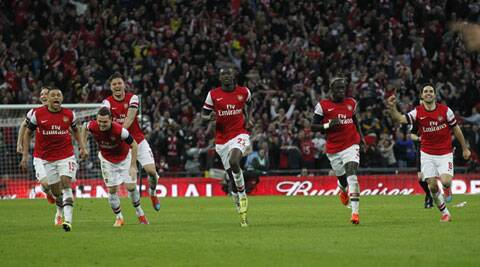 Arsenal players celebrate their win against Wigan Athletic after a penalty shoot-out during their FA Cup semifinal matchin London on Saturday. (AP)