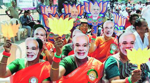BJP supporters wear masks of Narendra Modi during an election campaign rally in Coimbatore Tuesday. PTI